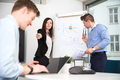 Businesswoman Pointing At Male Colleague Using Laptop - PhotoDune Item for Sale