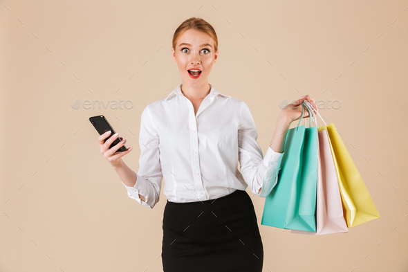 Emotional young business woman holding shopping bags using mobile phone. - Stock Photo - Images