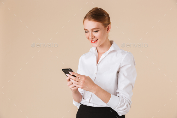 Cheerful young business woman using mobile phone. - Stock Photo - Images
