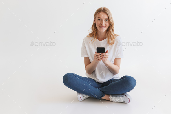 Pretty young cute redhead woman using mobile phone. - Stock Photo - Images