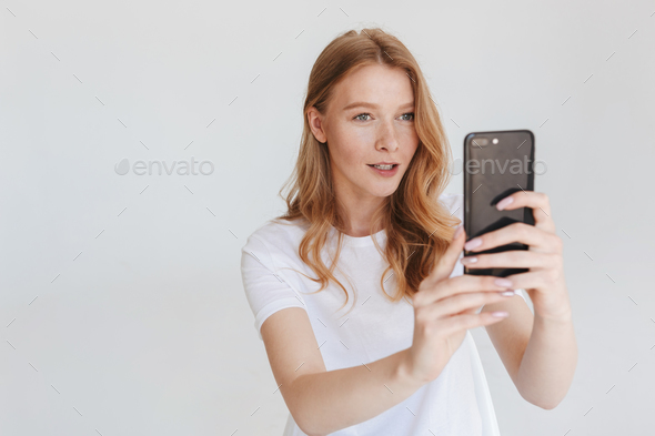 Redhead woman isolated using mobile phone make photo. - Stock Photo - Images