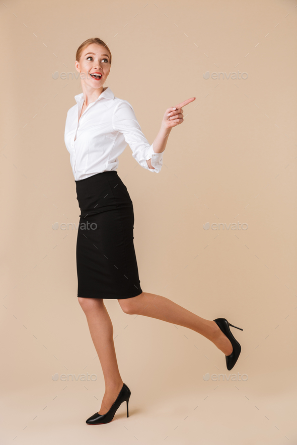 Happy amazing young business woman pointing. - Stock Photo - Images