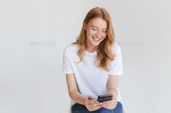 Redhead happy woman using mobile phone. - Stock Photo - Images