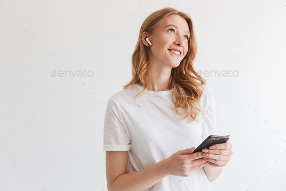 Happy young redhead woman listening music with earphones by mobile phone. - Stock Photo - Images