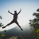 Hiker jumping on sunrise mountain top cliff edge - PhotoDune Item for Sale