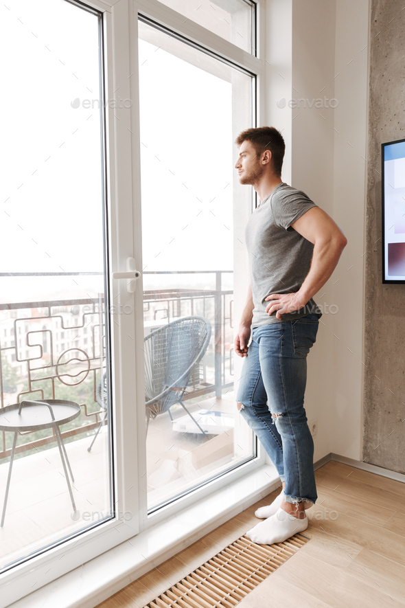 Pensive young man standing at the window - Stock Photo - Images