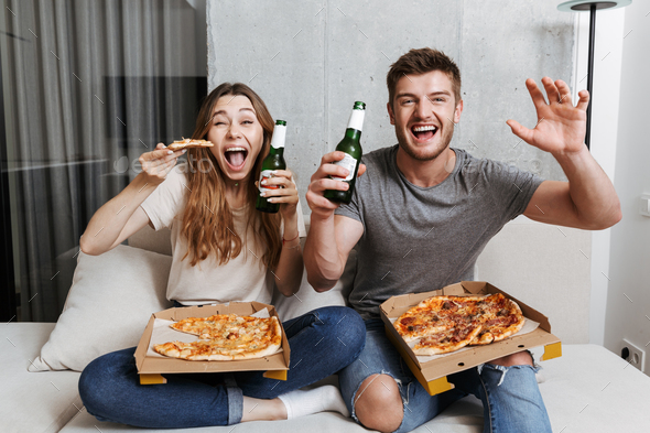 Excited young couple eating pizza and drinking beer - Stock Photo - Images