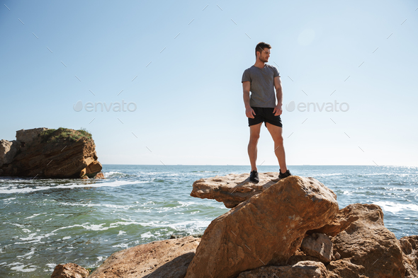 Young sportsman standing at the seashore on a rock - Stock Photo - Images