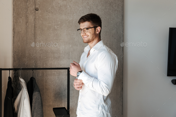 Confident young man putting on white shirt - Stock Photo - Images