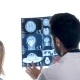 Dcotor with a Patient Checking a MRI Scan in Front of Big White Dispaly - VideoHive Item for Sale