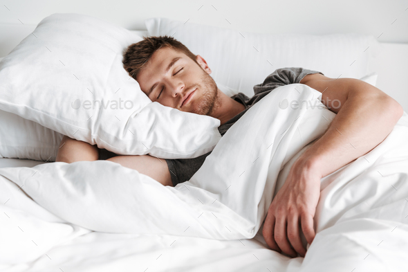Handsome young man sleeping in bed - Stock Photo - Images