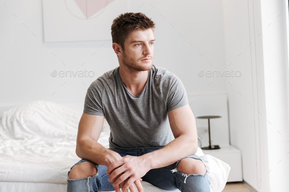 Concentrated young man sitting on his bed at home - Stock Photo - Images
