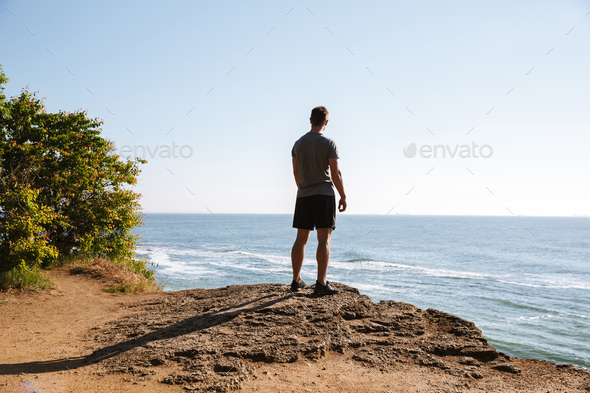 Young sportsman standing at the seashore and looking - Stock Photo - Images