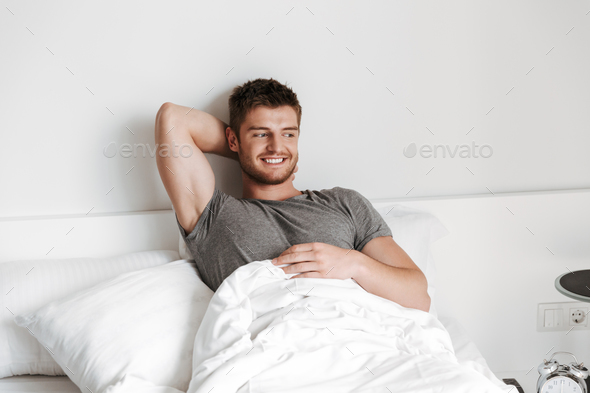 Attractive young man sitting in bed - Stock Photo - Images