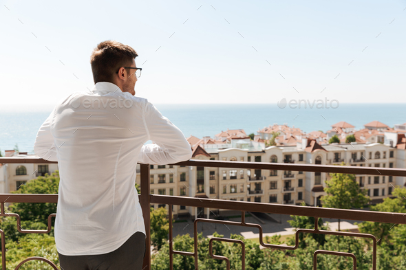 Back view of a young man standing on a balcony - Stock Photo - Images