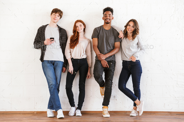 Smiling young friends students over white wall - Stock Photo - Images