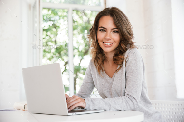 Cheerful young lady sitting in classroom - Stock Photo - Images