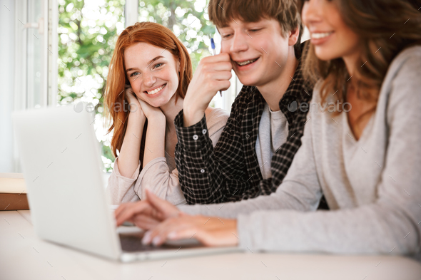 Smiling young friends students using laptop computer. - Stock Photo - Images