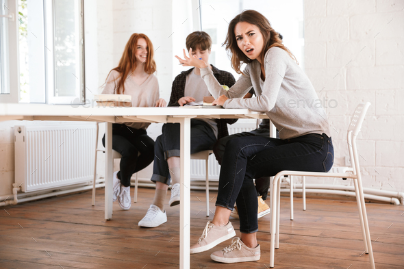 Displeased young woman writing notes - Stock Photo - Images