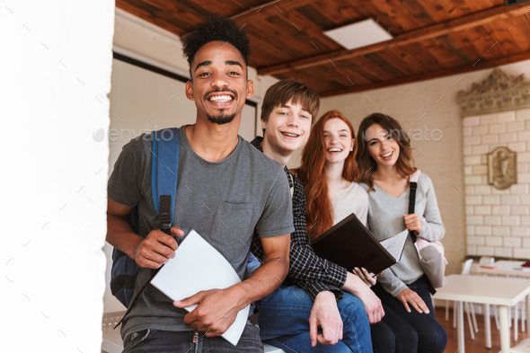 Cheerful group of friends students in classroom - Stock Photo - Images