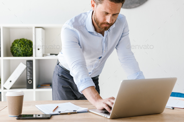 Concentrated handsome bearded man using laptop computer. - Stock Photo - Images