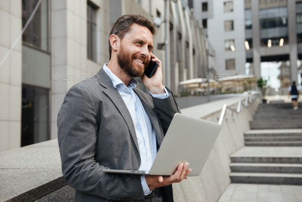 Photo of smiling businesslike man 40s in gray suit holding open - Stock Photo - Images