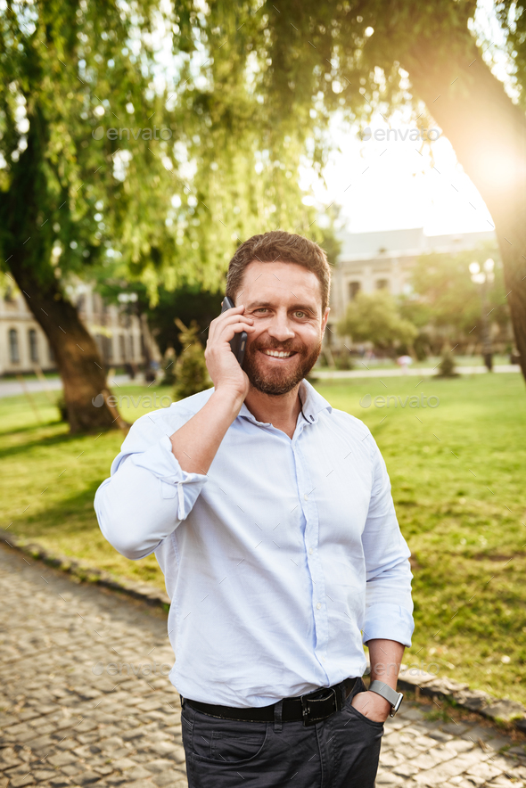 Photo of joyful guy 30s, walking in city park on sunny day and s - Stock Photo - Images
