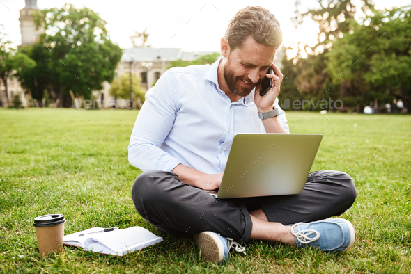 Photo of adult european man in business clothing, sitting on gra - Stock Photo - Images