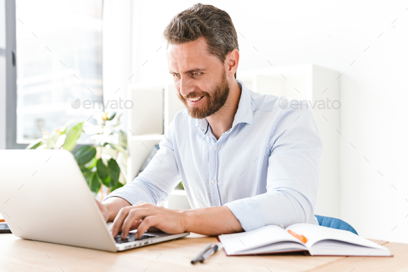 Happy bearded man sitting in office - Stock Photo - Images