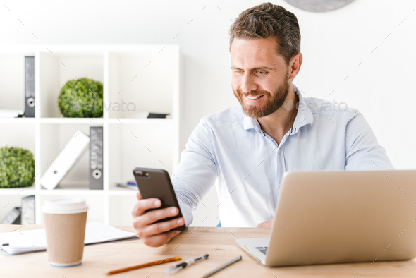 Happy handsome bearded man using mobile phone and laptop computer. - Stock Photo - Images