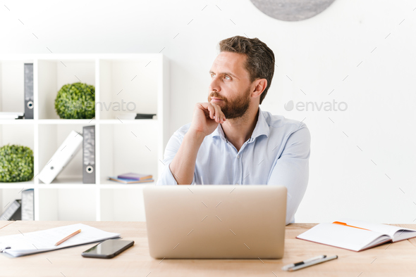 Concentrated bearded man sitting in office - Stock Photo - Images