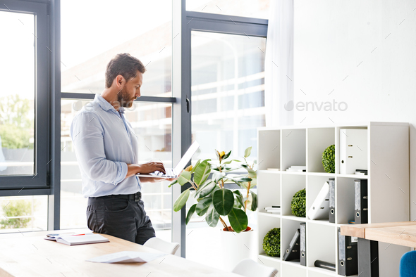 Handsome bearded man in office using laptop computer working looking aside. - Stock Photo - Images