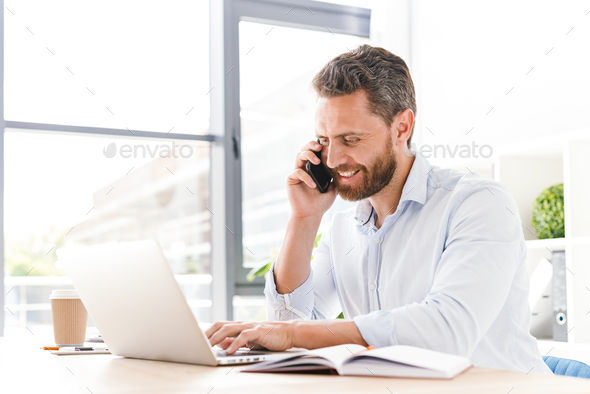 Happy handsome bearded man talking by mobile phone while using laptop computer. - Stock Photo - Images