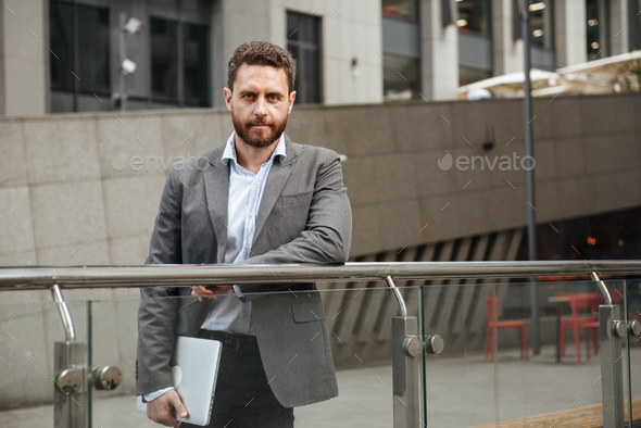 Image of confident business man 40s in formal wear holding close - Stock Photo - Images