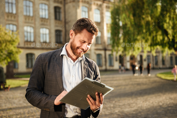 Image of successful businessman 40s holding clipboard and examin - Stock Photo - Images
