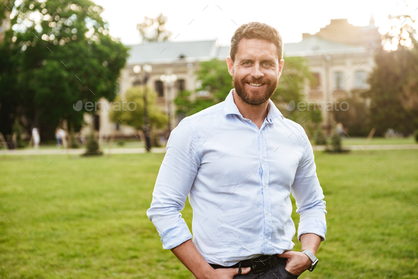 Portrait of european attractive man in white shirt, standing wit - Stock Photo - Images