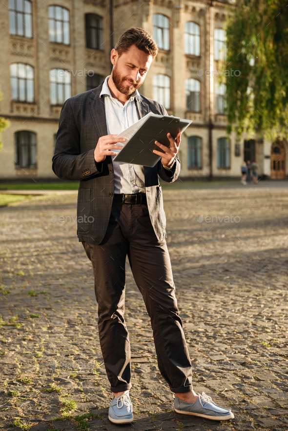 Full length photo of businesslike man in formal wear, holding cl - Stock Photo - Images
