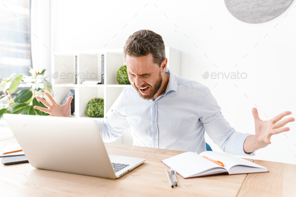 Agressive bearded man sitting in office working - Stock Photo - Images