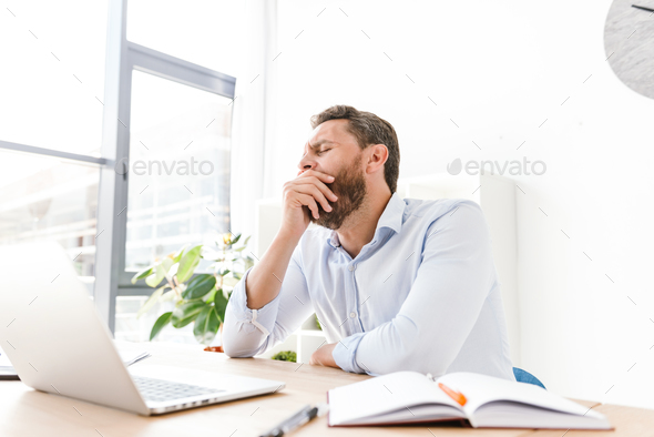 Tired yawning bearded man sitting in office - Stock Photo - Images