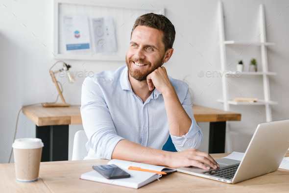 Happy bearded man sitting in office working - Stock Photo - Images