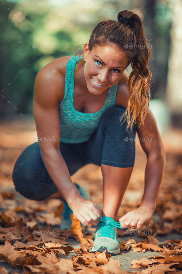 Woman tying shoe in the Park - Stock Photo - Images