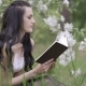 Young Woman Reading a Book Outdoor Leaning Against Tree Relaxing Hobby