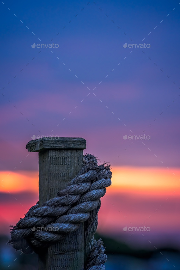 Thick rope tied around a wooden fence - Stock Photo - Images