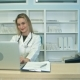 Smiling Medical Nurse Working on Laptop and Making Notes at Reception Desk - VideoHive Item for Sale