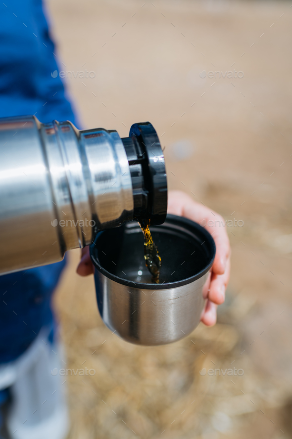 Woman pouring hot tea from a thermos on a sandy beach on a Sunny day. Close up. - Stock Photo - Images