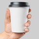 Mockup of men's hand holding white paper mid size cup with black cover - PhotoDune Item for Sale