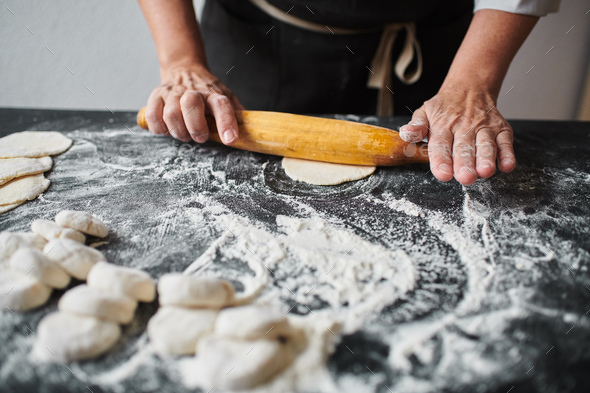 Woman rolling the dough by hands - Stock Photo - Images