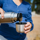 Woman pouring hot tea from a thermos on a sandy beach on a Sunny day. Close up. - PhotoDune Item for Sale