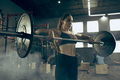 Fit young woman lifting barbells working out in a gym - PhotoDune Item for Sale