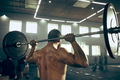 Fit young man lifting barbells working out in a gym - PhotoDune Item for Sale